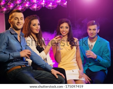 Group of cheerful young friends sitting with drinks at night club - stock photo