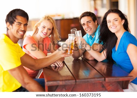 group of cheerful young friends toasting in a bar - stock photo