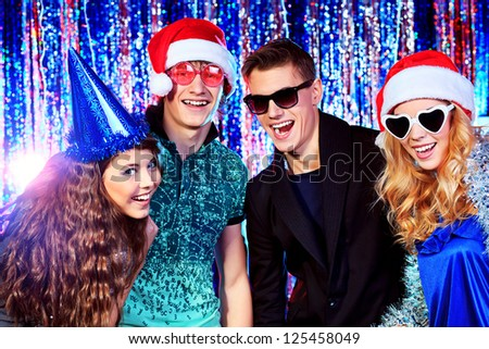 Group of cheerful young people celebrating Christmas at the nightclub.