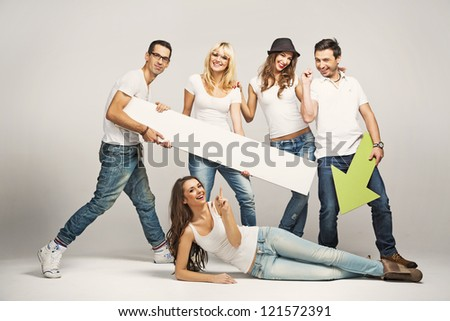 Group of cheerful young people holding empty board - stock photo