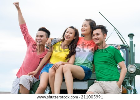 Group of cheerful young people sitting on the car hood and enjoying the view - stock photo