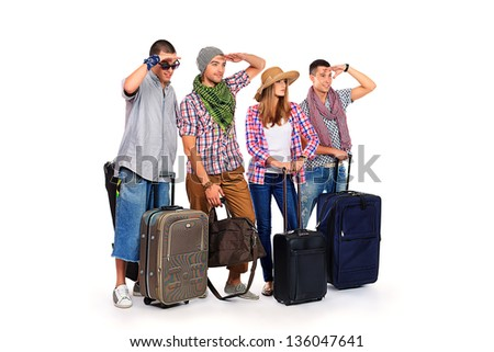 Group of cheerful young people standing together with suitcases over white background.