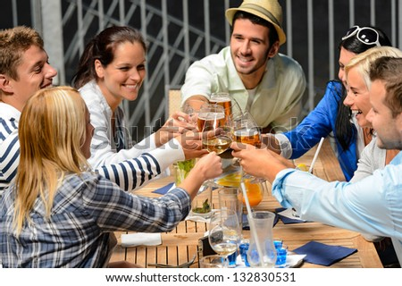 Group of cheerful young people toasting with drinks night out - stock photo