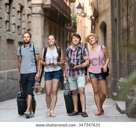 Group of cheerful young travelers walking through the city with travel bags. Selective focus