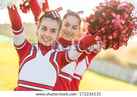 Group of Cheerleaders with Raised Pompom - stock photo