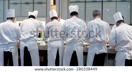 Group of chefs in white uniform busy to preparing food for they client - stock photo