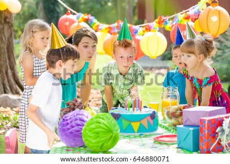 Group of children and animator blowing off he candles from the cake