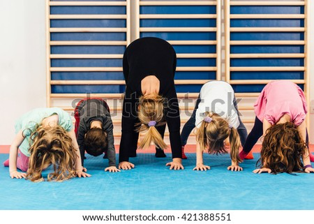 Group of children at physical education, exercising with teacher - stock photo