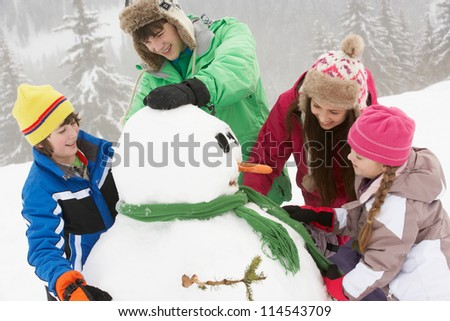Group Of Children Building Snowman On Ski Holiday In Mountains - stock photo