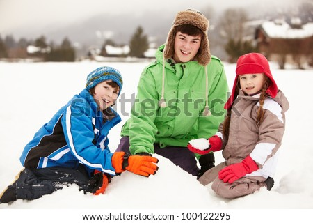 Group Of Children Building Snowman Wearing Woolly Hats - stock photo