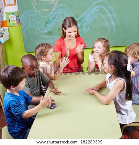 Group of children clapping hands in kindergarten in musical education class - stock photo
