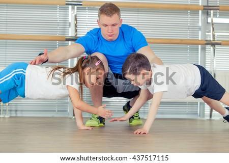 Group of children doing kids gymnastics in gym with nursery teacher - stock photo