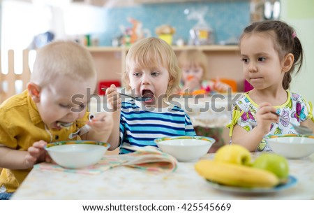 group of children eating from plates in day care centre - stock photo