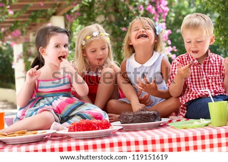 Group Of Children Eating Jelly And Cake At Outdoor Tea Party - stock photo