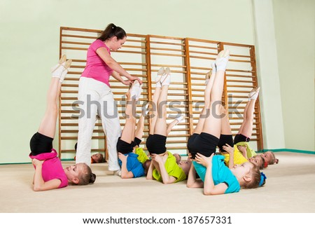 Group of children engaged in physical training in gym - stock photo