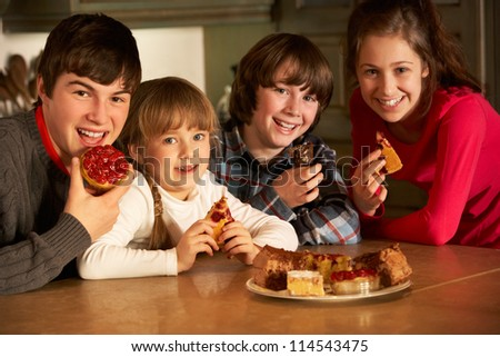 Group Of Children Enjoying Plate Of Cakes In Kitchen