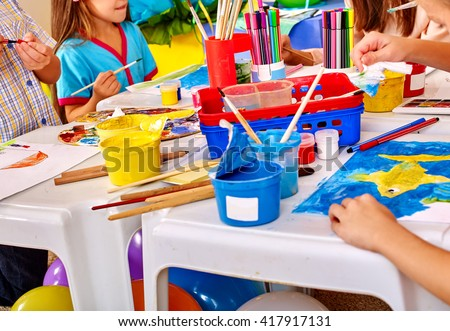 Group of children hands  painting on paper at table  in  kindergarten . Paint lesson. - stock photo