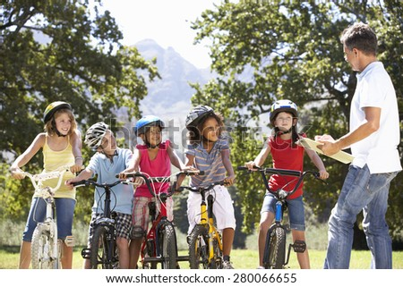 Group Of Children Having Safety Lesson From Adult Whilst Riding Bikes In Countryside