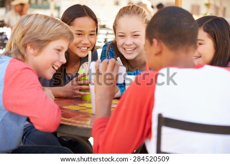 Group Of Children In Caf\x81_ Looking At Text On Mobile Phone - stock photo
