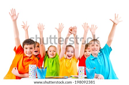 Group of children in colored t-shirts sitting at a table with raised hands.