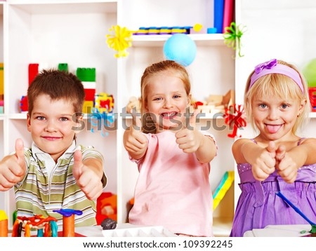 Group of children  in preschool thumb up. - stock photo