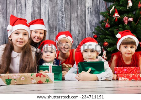 Group of children in santa claus hats with presents  - stock photo
