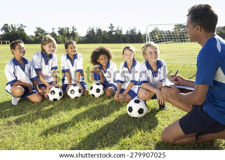 Group Of Children In Soccer Team Having Training With Coach - stock photo