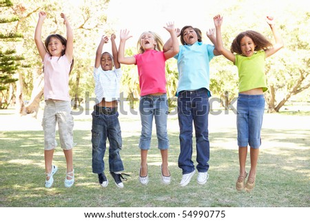 Group Of Children Jumping In Air In Park - stock photo