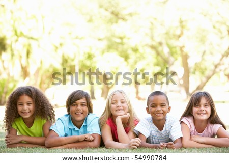 Group Of Children Lying On Stomachs In Park - stock photo