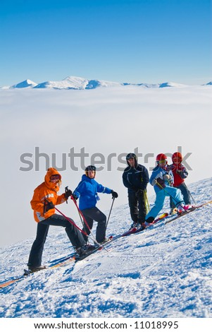 Group of children-mountain skiers on a slope of mountain Stig above a fog together with the trainer - stock photo