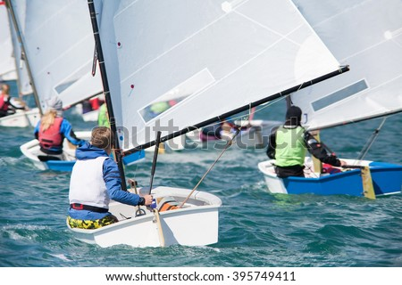 group of children on sailing boats competing in the regatta at sea - stock photo