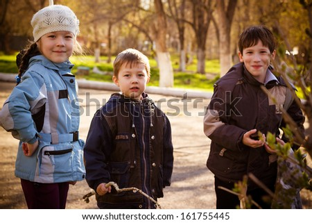 Group of children on walk in park in the autumn afternoon - stock photo
