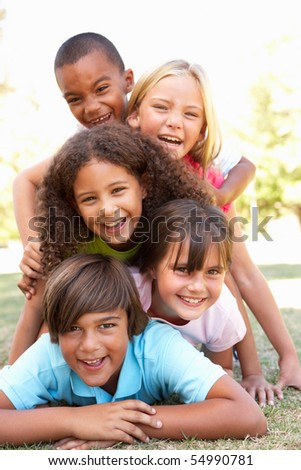 Group Of Children Piled Up In Park - stock photo