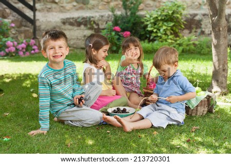 Group of children playing and having a picnic in a backyard