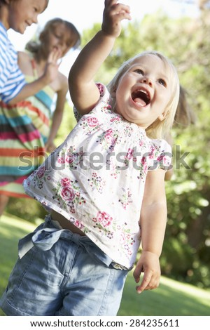 Group Of Children Playing In Garden - stock photo