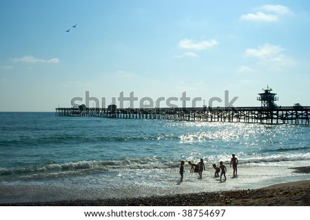 Group of children playing in the Pacific Ocean near the San Clemente Pier in Southern California. - stock photo