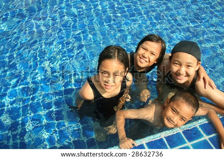 Group of children playing in the pool. - stock photo