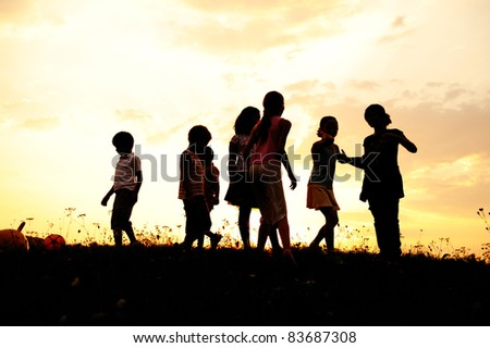 Group of children playing on meadow, sunset, summertime