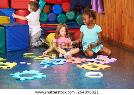 Group of children playing together in a kindergarten - stock photo