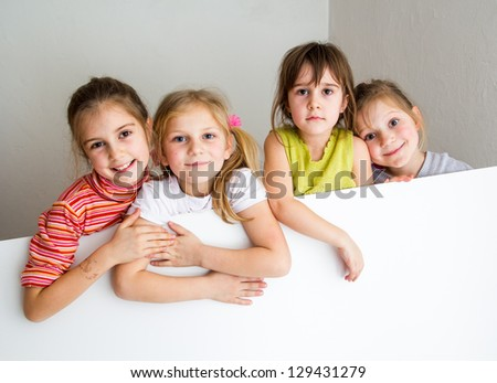 Group of children posing and hiding behind a large white table - large copy-space - stock photo