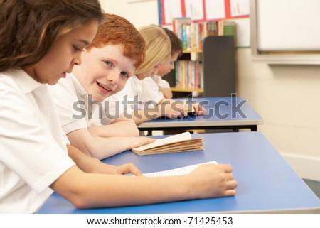 Group Of Children Reading Books In Classroom - stock photo
