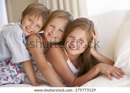 Group Of Children Relaxing On Sofa At Home