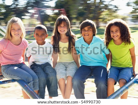 Group Of Children Riding On Roundabout In Playground - stock photo