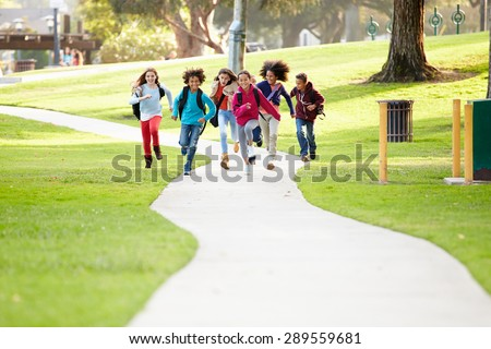 Group Of Children Running Along Path Towards Camera In Park - stock photo