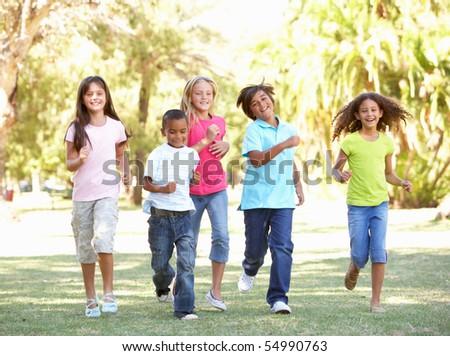 Group Of Children Running Through Park - stock photo