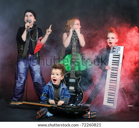 Group of children singing in heavy metal style. Shot in a studio. - stock photo