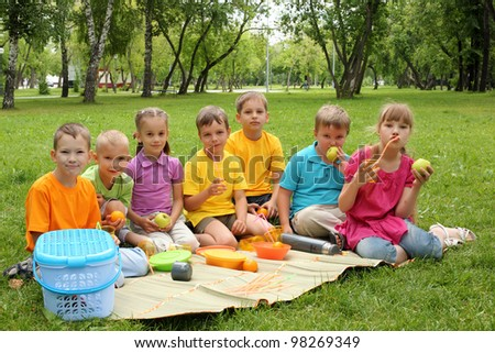 Group of children sitting together on teh grass in the park - stock photo