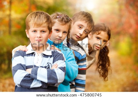Group of children standing in a row in a beautiful park full of autumn colours