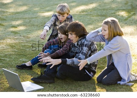 Group of children (10 to 15 years) shocked and fascinated by computer laptop - stock photo