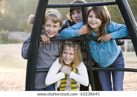 Group of children (10 to 15 years) standing together on playground on chilly day - stock photo
